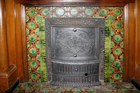 The cast iron fireplace insert, with its ornate 'summer front' is surrounded by the green and brown majolica tiles.