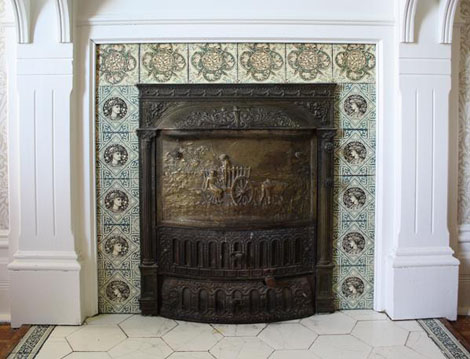 The tiles on this fireplace are a combination of two designs. Two variations of ladies' faces and six top tiles of intertwined branches and flowers add interest. If you look closely, you can see that the bottom left 'face' tile matches those on the right of the fireplace, and not those four tiles above it.