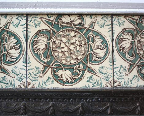 Above the cast iron fireplace insert are six tiles of a rustic design, with intertwined branches and sprays of flowers in both the centre design and at the corners of each tile.