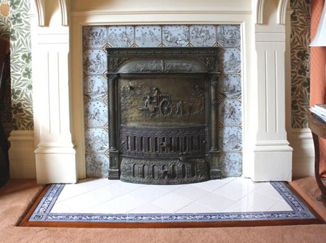 "The tiles surrounding the cast iron [with bronze wash] insert are a set of rare ""Sporting"" tiles dating from approximately 1886 from the Minton pattern book."