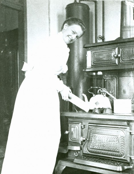 "A rare kitchen photograph from Victoria, B.C. c1900, showing the lady of the house at her ""NEW HOUSEHOLD"" range. A hot water tank is behind, connected to the stove to provide hot water for washing and bathing."