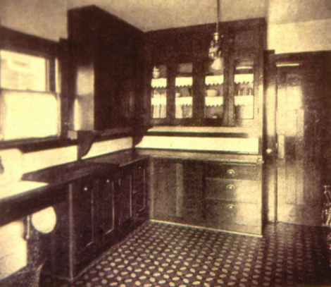 """An early installation of kitchen cupboards c1905. Wood counter tops and sink drains were common to begin with. Note the lack of 'toe-kick' space. The floor is patterned linoleum. Here it is a 'mosaic' lino, which was popular through the 1890's into the 1910's. Small pieces of different coloured lino were glued into patterns at the factory and available in rolls. Printed linoleums became popular – known as """"Art squares"""" - from 1905 through the 1920's and later."""