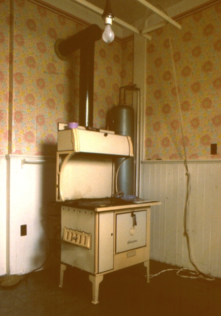 An unchanged kitchen in an 1893 house with original wainscoting and a 1920's stove. Note the drying rack over the stove controlled by a pulley system and a towel rack behind the stove. Photograph taken 1983.