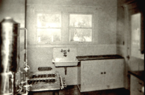An early photograph of a kitchen with gas burning range, connected to a hot water tank, supplying hot water to the kitchen sink, as well as the bathtub elsewhere in the house.